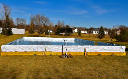 A backyard outdoor rink has been created with lighting for future skating and hockey.