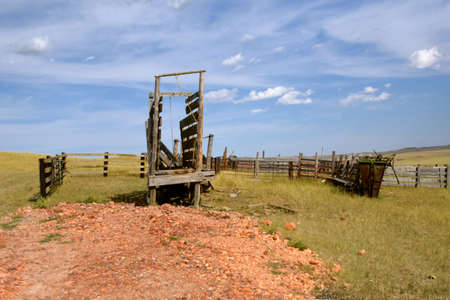 A cattle chute remains in front of an old wooden western corral