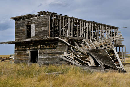 A deserted two story building in a prairie ghost town setting has fallen into total ruins Reklamní fotografie