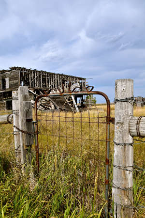 An old metal gate leads into the weedy long grassed deserted building site on the western prairie.