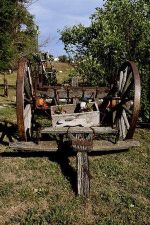 An old rickety wooden wagon serves as decoration in a rural backyard. Reklamní fotografie