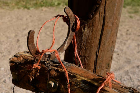 An old rusty horseshoe attached to a gate post and tied with orange baling twine serves as a handle