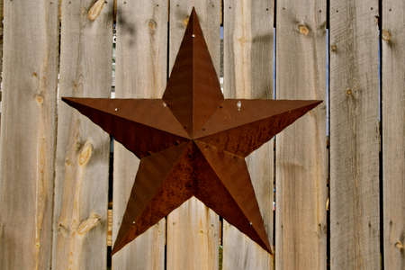 A rusty metal barn star is displayed on a weathered wood wall Reklamní fotografie