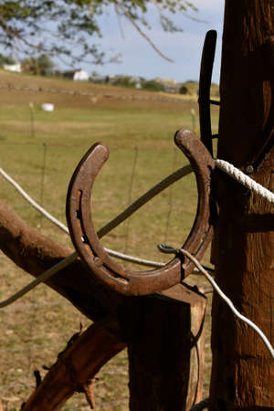 A rusty horseshoe attached to a gate serves as a handle in operating the opening and closing.