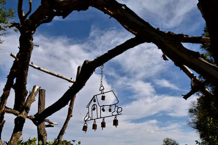 Wind chimes of a house are silhouetted as they hang from a tree branch