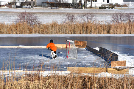A father /son practice hockey on a makeshift rink on a slough in the winter season Reklamní fotografie