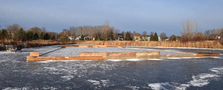 An outdoor skating rink creation in a pond of a suburban housing development (long and narrow)