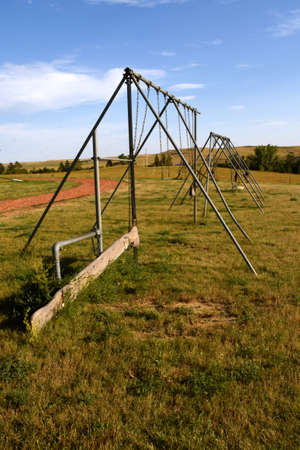 An old swing set and teeter-totter in a playground display, age, wear, and tear.