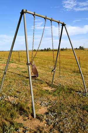 An old swing set in a playground displays age, wear, and tear.