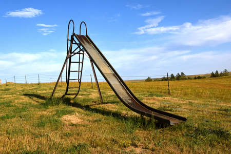 An old metal slippery slide remains in a playground in a ural western prairie setting.