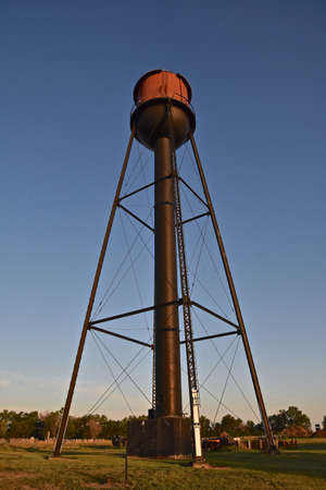 The early morning sun rays shine on an old town water tower.