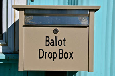 A ballot drop box is fastened to a door allowing voters to leave writing-in voting ballets. Reklamní fotografie