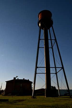 An old water tower and three story school building are silhouetted in the early morning light.