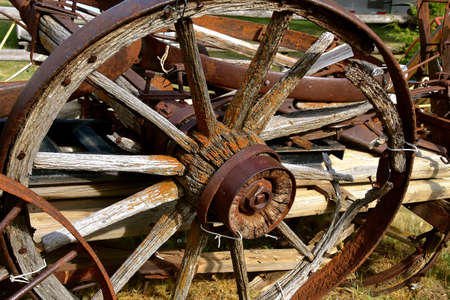 A close up of an old wooden, buggy wheel with spokes, hub, and axle.