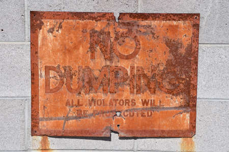 A very old rusty sign indicating violators will be prosecuted for dumping of debris.