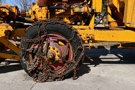 A wheel on a homemade snowblower is full of rusty chains and springs in an effort to gain traction.