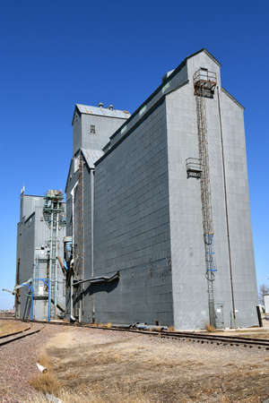 Alongside railroad tracks is s huge grain elevator complex with a caged ladder for climbing to the top Standard-Bild