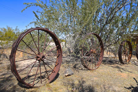 Very old metal spoked machine wheels serve as yard decorations and boundary line in a dry desert setting