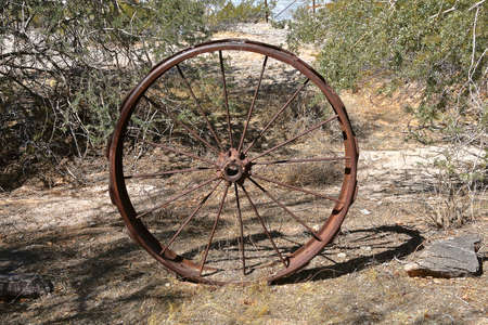 A very old metal spoked machine wheel serves as a  yard decoration in a dry desert setting