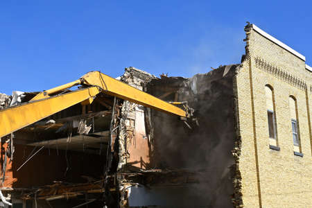 The arm of an excavating machine extends into the interior of a brick building in the process of demolition.