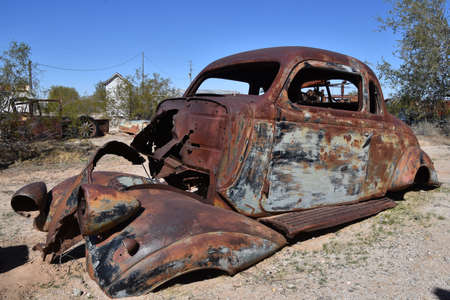 The remains of a very very old car full of patina resides in a junkyard and salvage company. Standard-Bild