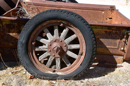 A very old wheel with wooden spokes, metal rim, and a rotten flat tire belong to a rusty box of a pickup or truck Standard-Bild
