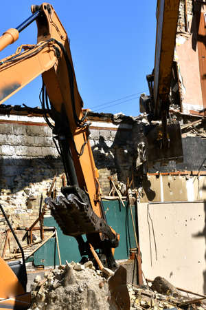 A huge shovel of a backhoe is in the processor scooping up a load of bricks in a demolition project.