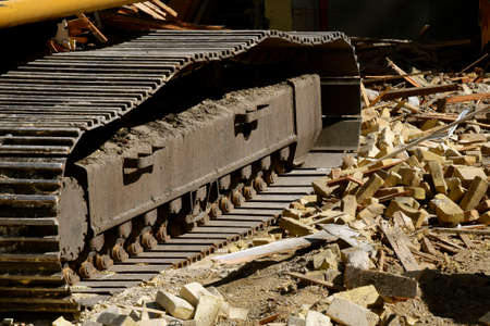 The track of a huge elating machine rests on debris of wood and bricks