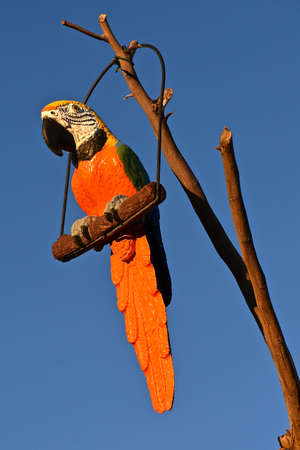 A wood carving of an orange parrot hangs from a branch