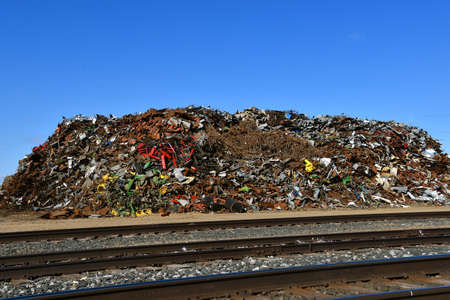 A huge pile of scrap metal and iron adjacent to railroad tracks ready to be loaded. Stock Photo