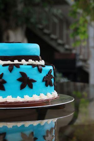 야외 설정에 유리 테이블에 파란색 계층 형 웨딩 케이크 스톡 콘텐츠