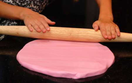 Child rolling out pink fondant frosting on black granite surface Stockfoto