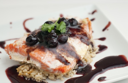 Baked salmon fillet with blueberry balsamic reduction on brown rice