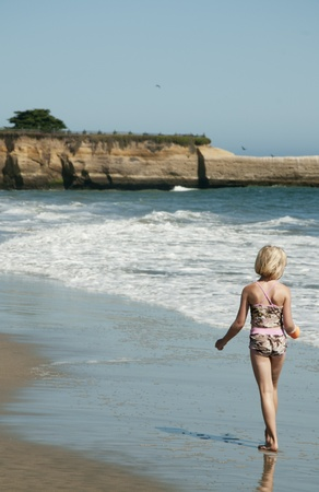 Blond little girl happily walking in the surf Foto de archivo
