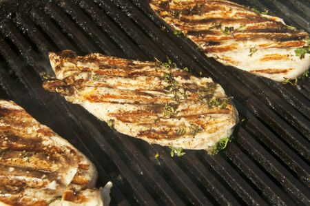 Chicken breasts with herbs salt and pepper on the grill Stockfoto
