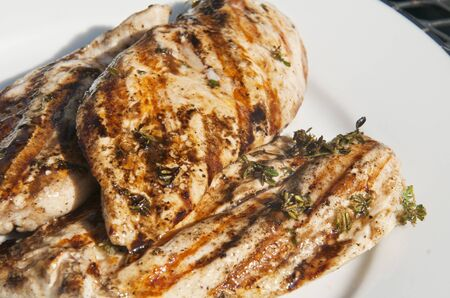 Grilled chicken breasts with herbs salt and pepper on white plate Stock fotó