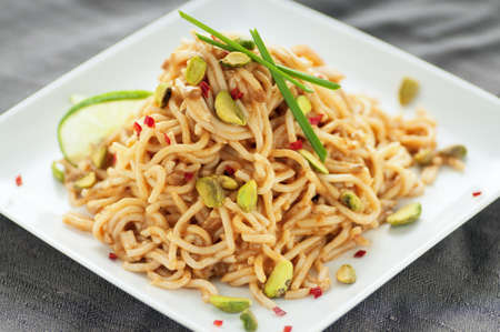 Pile of noodles in Oriental sauce with pistachio, fresh red chilis and garlic chives photo