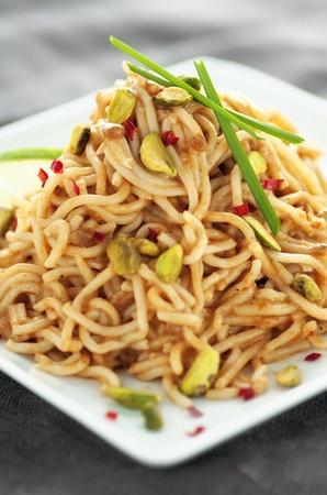 オリエンタル麺の山ピスタチオ、新鮮な赤い chilis およびニンニク チャイブ添え 写真素材 - 10566687