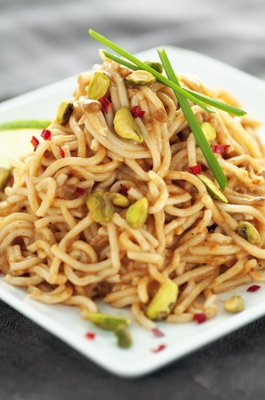 Pile of noodles in Oriental sauce with pistachio, fresh red chilis and garlic chives
