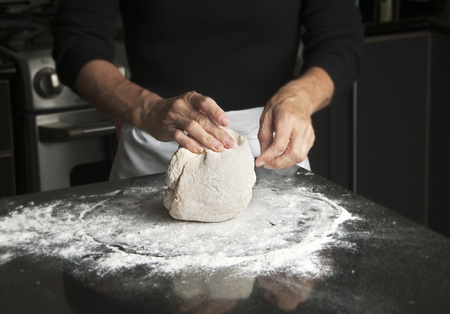 dough: Mujer en delantal negro de arriba y blanco amasando pasta en caldo de granito negro Foto de archivo