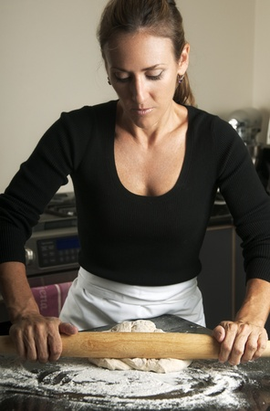 Beautiful pastry chef rolling out fresh dough photo