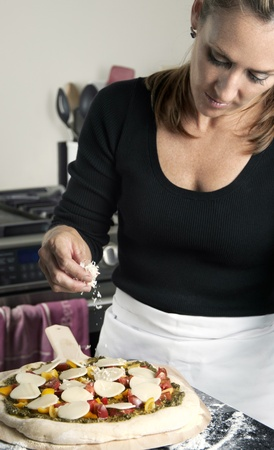 Woman sprinkling parmesan cheese on her pizza