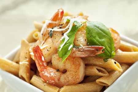 White square bowl of whole wheat penne pasta with sauteed shrimp and basil Stock Photo