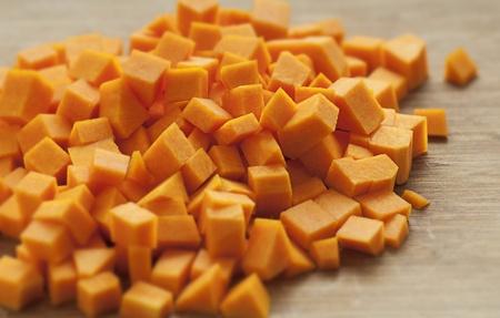 Chopped orange butternut squash on cutting board