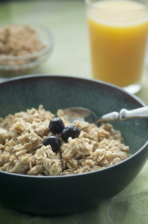 Hot bowl of porridge with blueberries and orange juice photo