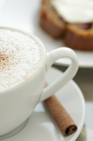 Cappuccino with cinnamon stick and fresh baked bread with butter