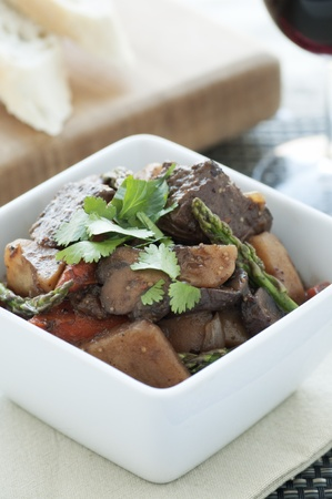 Fresh beef stew with asparagus and cilantro garnish
