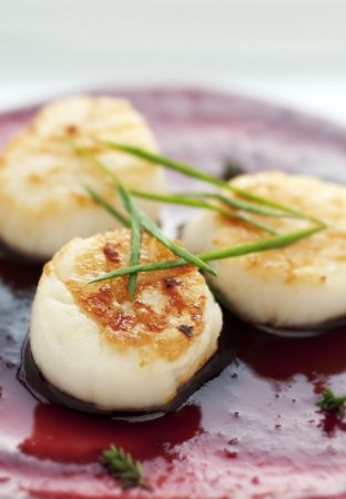 Perfectly seared scallop starter with bright cranberry and balsamic vinegar reduction photo