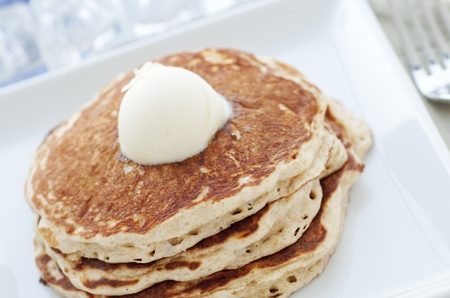 Fresh buttermilk pancakes with scoop of butter on white plate
