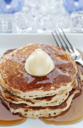 Fresh buttermilk pancakes with scoop of butter on white plate photo